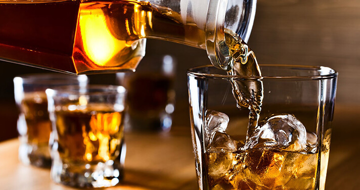pouring irish whiskey in glass